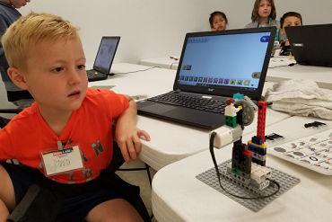 child looking at Lego robot in class